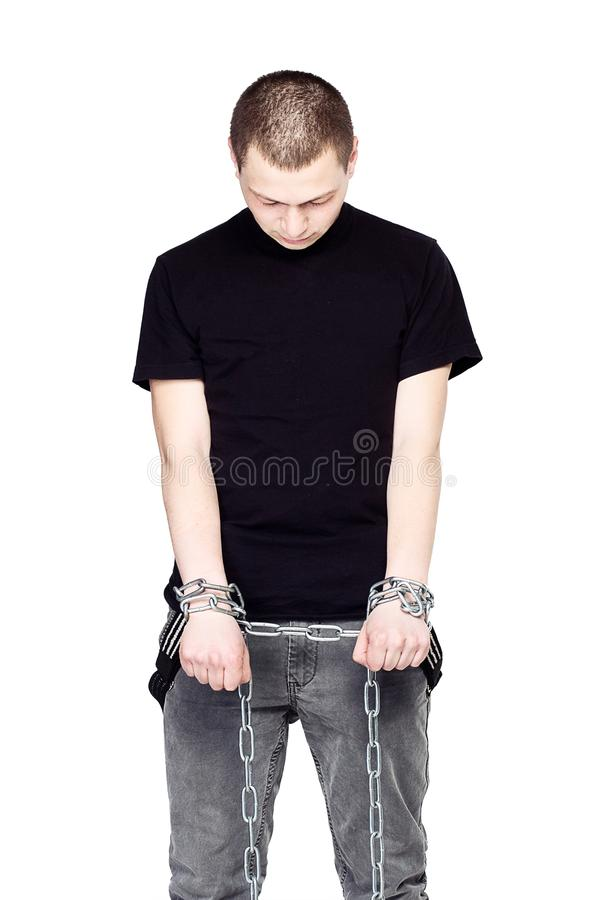 Man in iron chains look down. The concept of prison.  royalty free stock photos