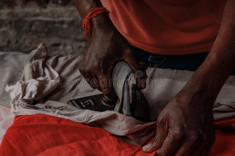 A man is ironing the cloth with an vintage iron stock photo