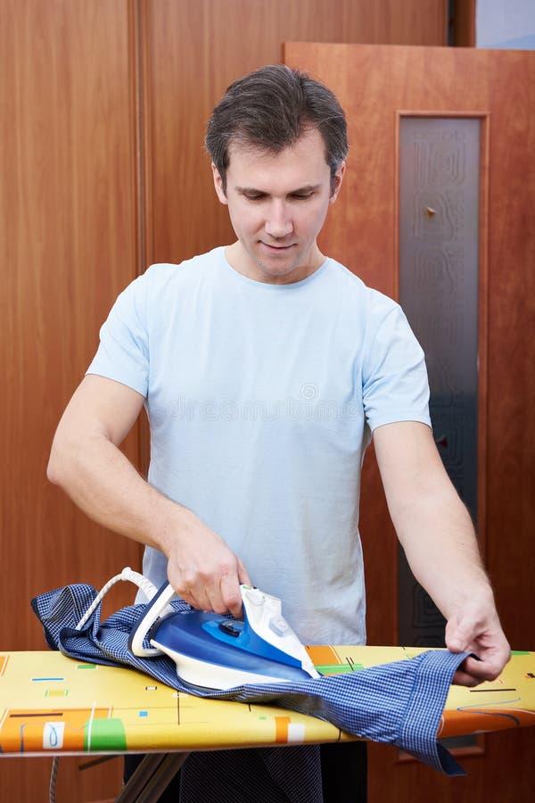 Man ironing his blue shirt royalty free stock photos