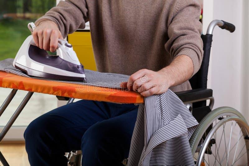 Man ironing his shirt stock photography