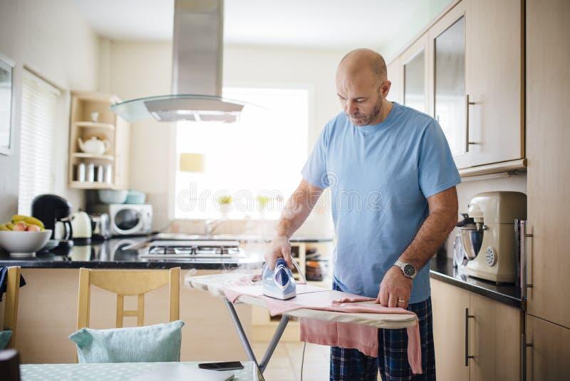 Man Ironing Laundry stock photo
