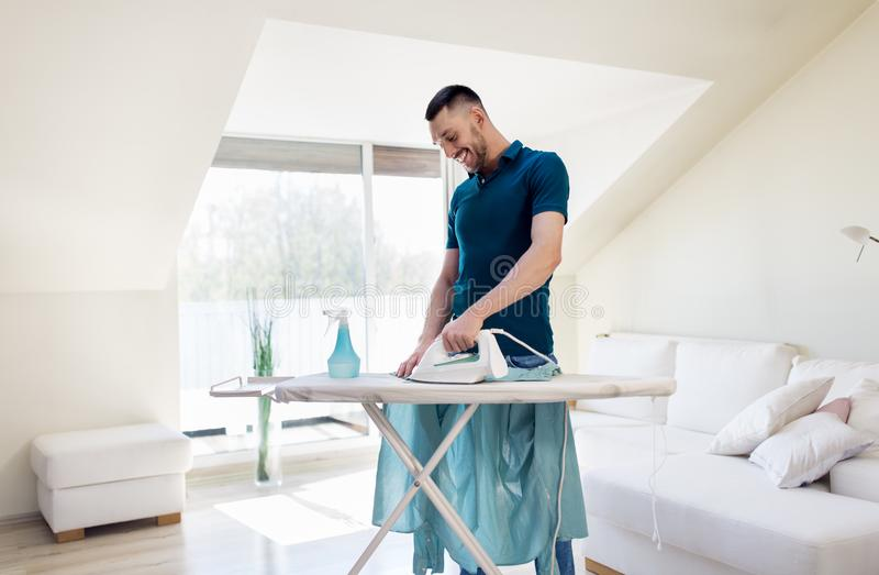 Man ironing shirt by iron at home. Housework and household concept - man ironing shirt on iron board at home royalty free stock photos