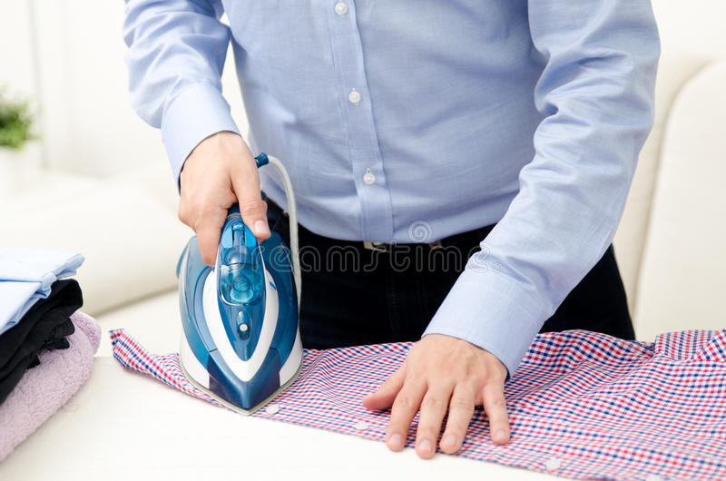 Man ironing shirt on ironing board with steaming blue iron. Man ironing shirt on ironing board. Steaming blue iron. Clothes ironing board household concept royalty free stock photos
