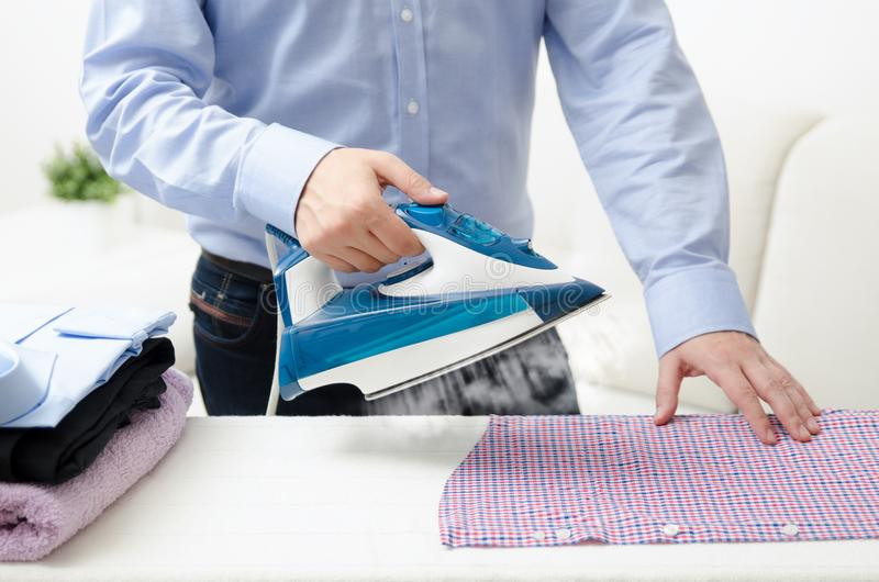Man ironing shirt on ironing board with steaming blue iron. Man ironing shirt on ironing board. Steaming blue iron. Clothes ironing board household concept stock photos
