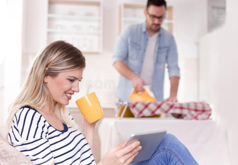 Man ironing while woman resting stock photography