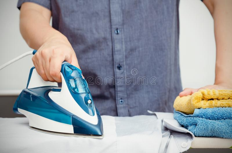 Man irons clothes on ironing board with blue iron. Man irons clothes on ironing board with steaming blue iron royalty free stock photos