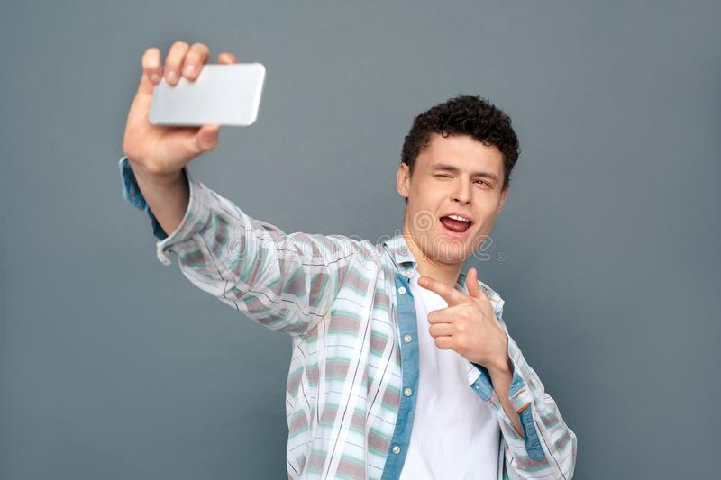 Man isolated on gray wall free style standing taking selfie photos on smartphone cool playful. Young guy isolated on gray wall free style standing holding stock photography