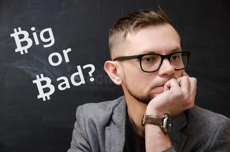 Man in a jacket and glasses on the background of black school board on which it is written Big or Bad? royalty free stock photo