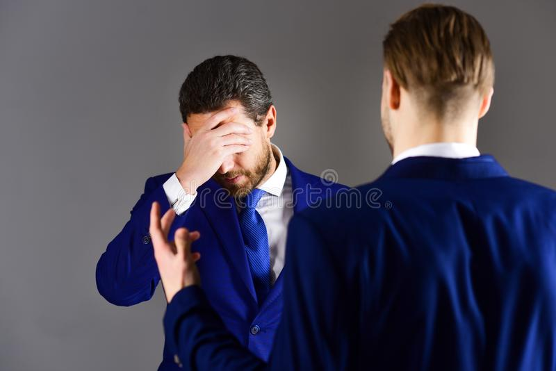 Man in jacket listening his business partner with desperate expr. Ession. Boss and employee speaking at meeting on dark background. Difficulties in business stock photography