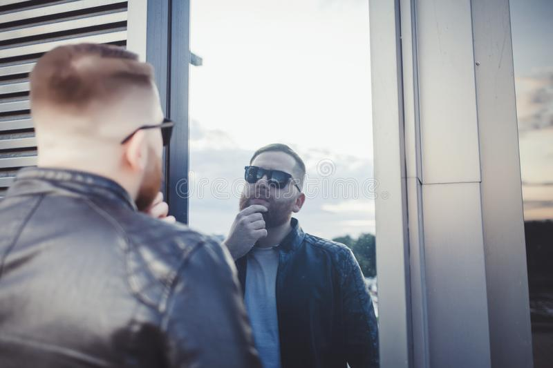 Man in jacket looks in the mirror stock image