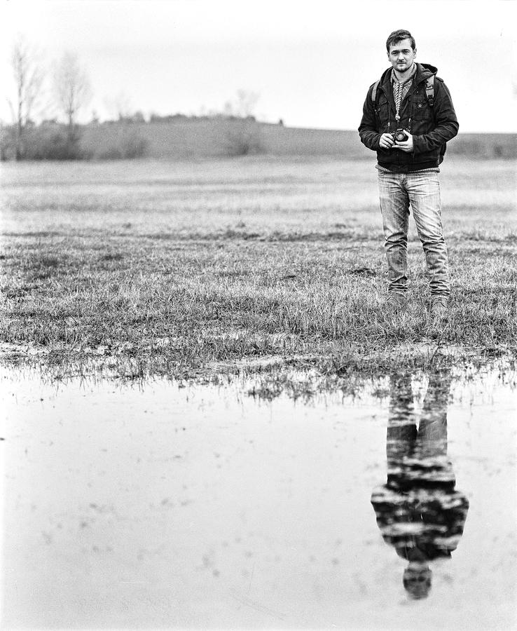Man In Jacket Standing Near Body Of Water Holding Camera In Grayscale Photography Free Public Domain Cc0 Image