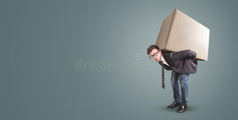 A man is carrying a large cardboard box - isolated on a neutral background with copy space. A man in a jacket and tie is standing bent over with a large royalty free stock photo