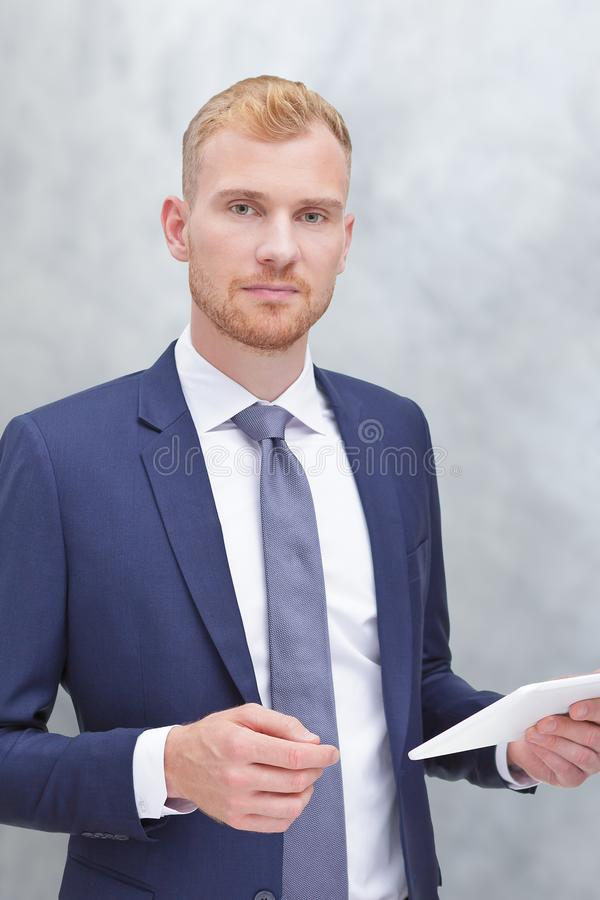 Man jacket tie tablet computer. Modern portrait of an adult man with tablet computer, insurance agent, bank advisor or tax consultant stock photo