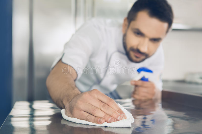 Man japanese restaurant chef working in the kitchen. Male japanese restaurant chef working in the kitchen cleaning royalty free stock photo