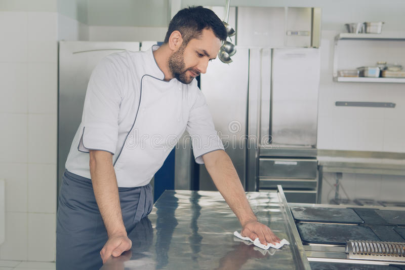 Man japanese restaurant chef working in the kitchen. Male japanese restaurant chef working in the kitchen cleaning royalty free stock image