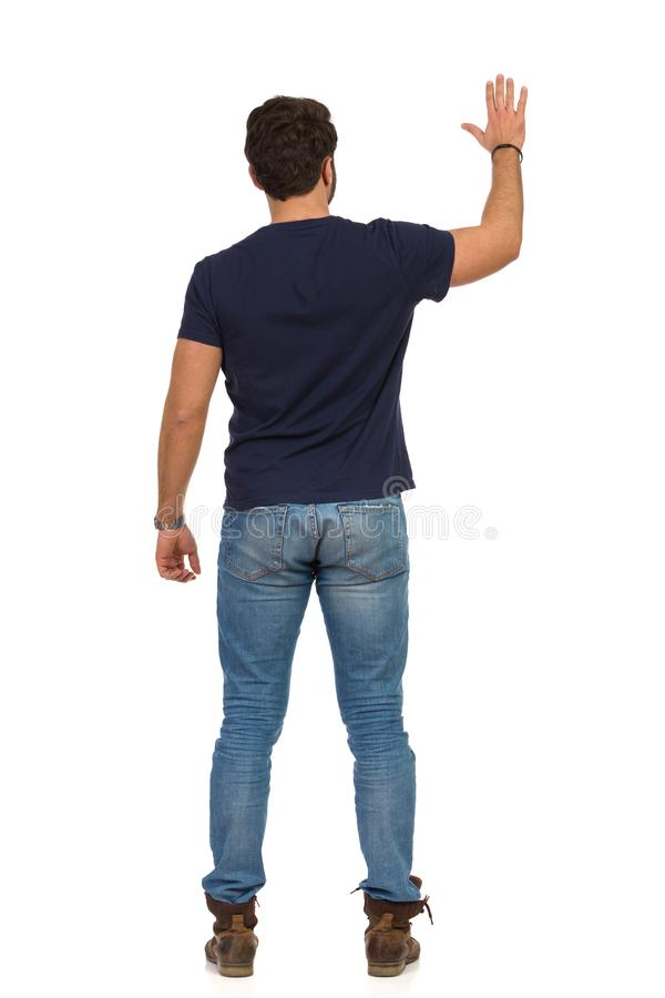 Man In Jeans And Blue T-shirt Is Standing With Arm Raised And Waving Hand. Rear View. Full length studio shot isolated on white stock photos