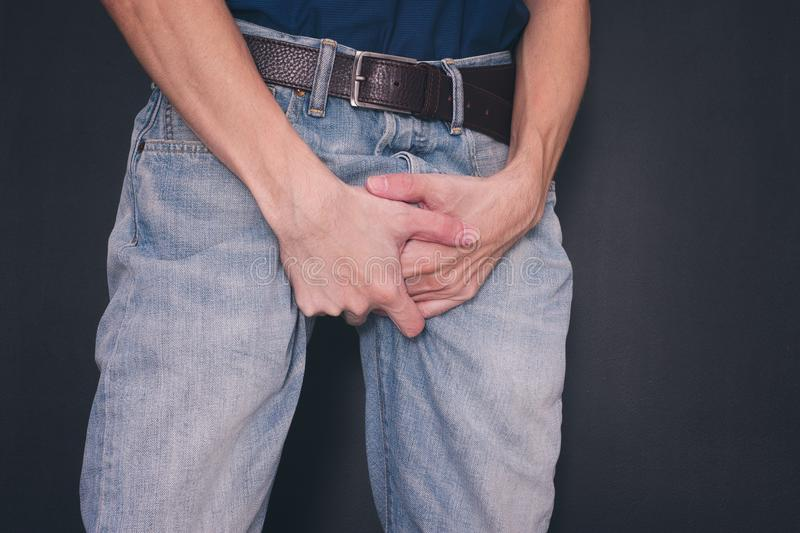 Man in jeans covers his crotch with hands. Close up royalty free stock photography