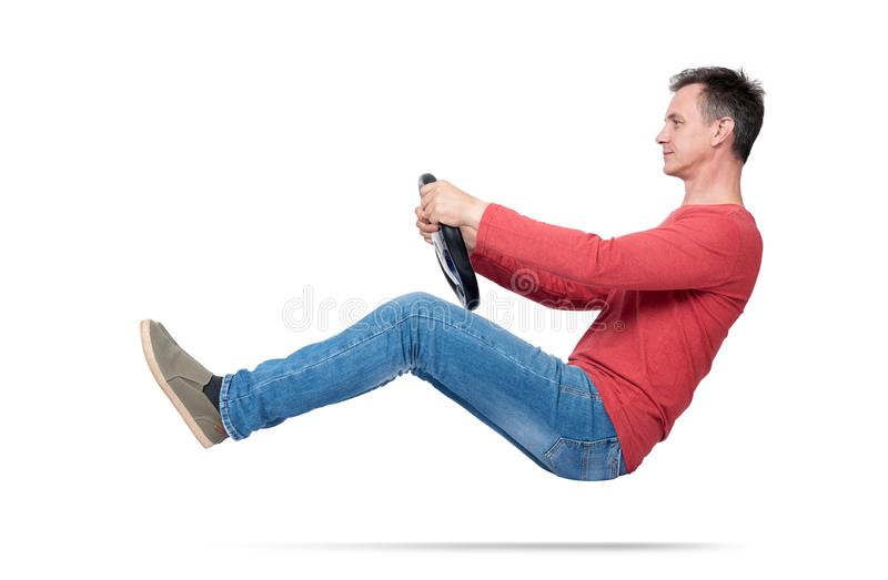 Man in jeans and red t-shirt drives a car with a steering wheel, isolated on white background. Auto driver concept stock images