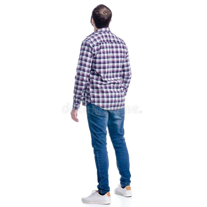 A man in jeans and shirt looks up stock images