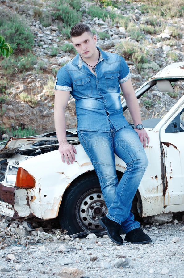 Man in jeans, sitting on an old damaged car. Man in jeans, facing the camera, sitting on an old damaged car. Full length and vertical photo royalty free stock image