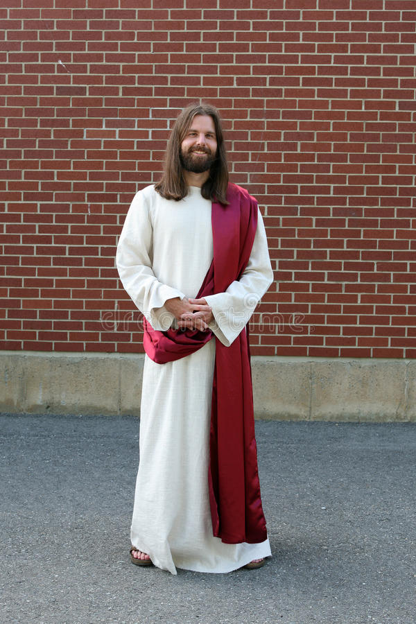 Man in Jesus robe and sash next to brick wall stock photo