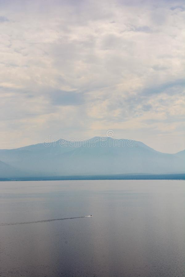 Jet Skiier whizzing across Lake Tahoe in Hazy Smoke From Wildfire. Man jet skiing across hazy lake Tahoe with mountains in background. The lake is hazy from a stock photos