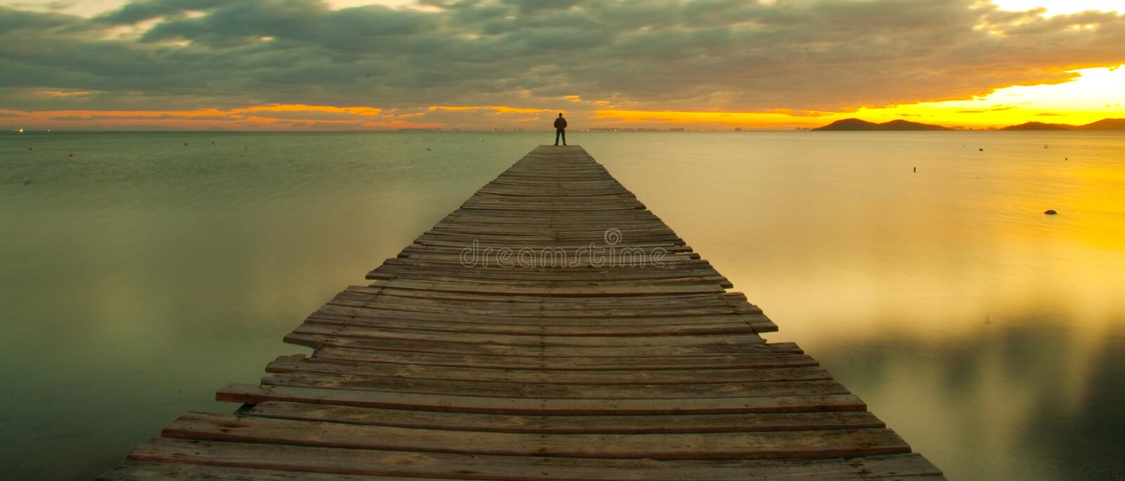 Man on jetty at sunset stock photography