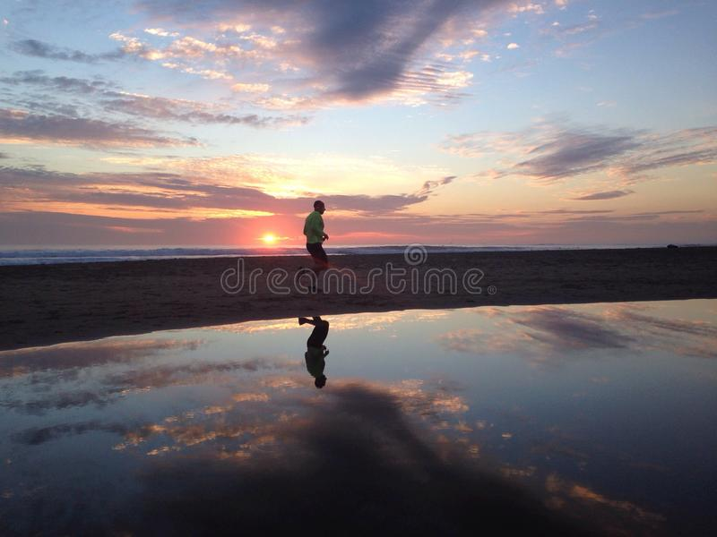 Man jogger running on sunset beach with reflection royalty free stock photo