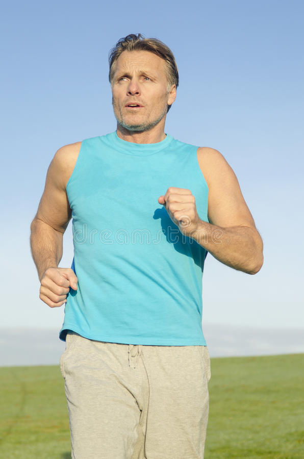 Man Jogging In Blue Shirt Stock Photography