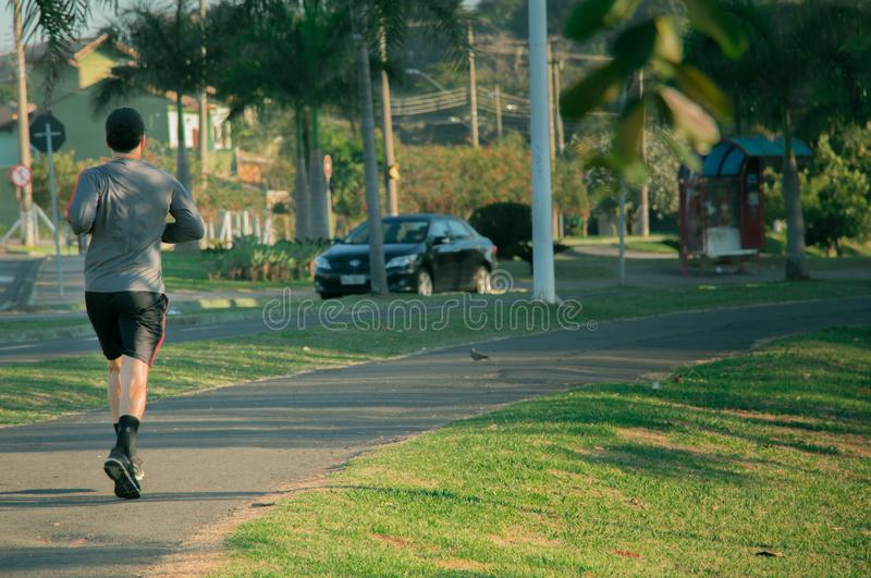 Man jogging at the park in the morning. Showing a healthy lifestyle with a lot of exercising. stock images