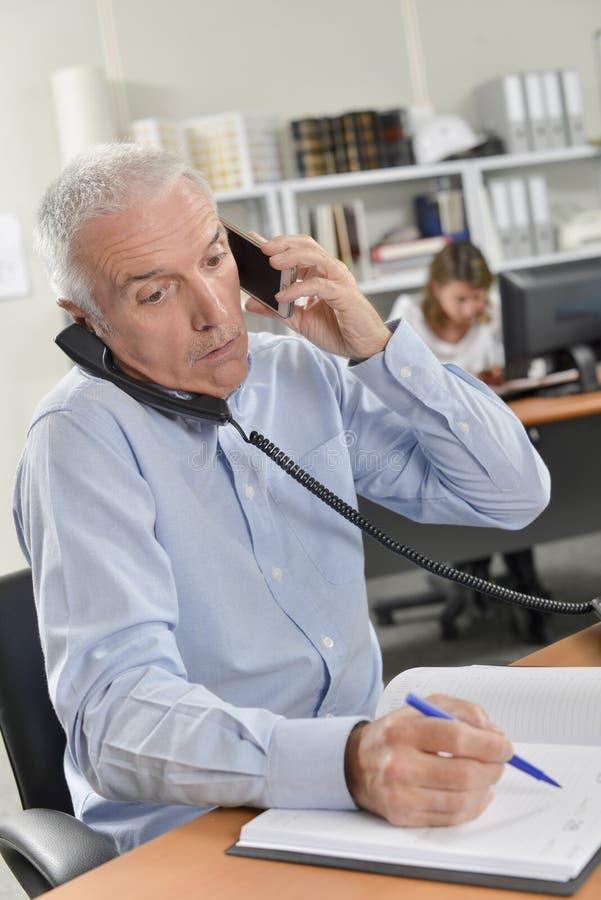 Man juggling several telephone conversations royalty free stock image