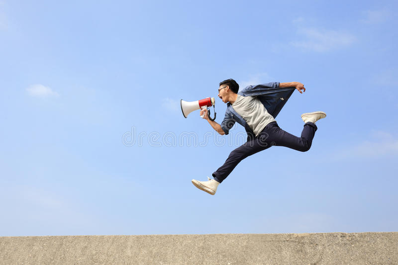 Man jump and shout megaphone. Man jump and shout by megaphone with blue sky background, asian royalty free stock image
