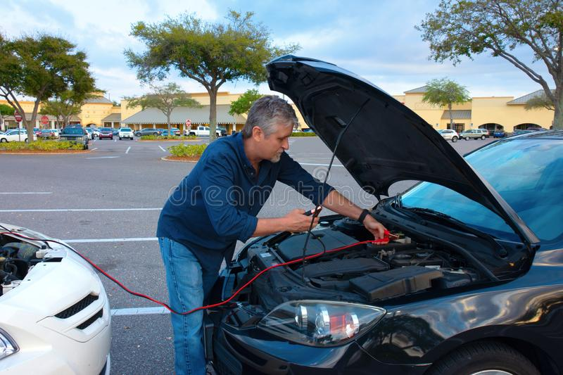 Man jump starting a car with jumper cables stock images
