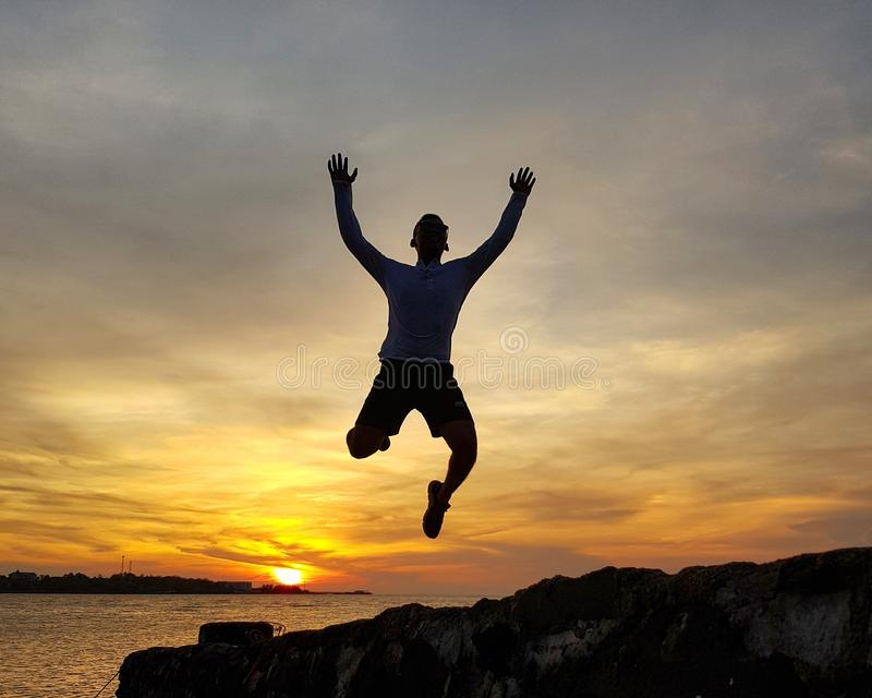 Man jumping on beach  against sunset sky royalty free stock image
