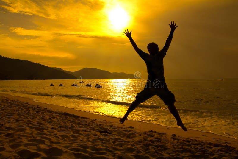 Man jumping on beach sunset. Silhouette happy man jumping on the beach during sunset stock photo