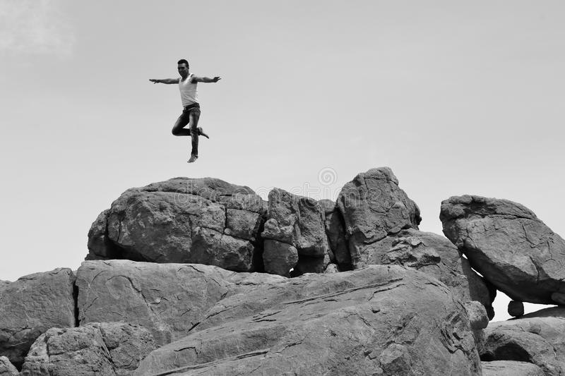Man jumping or dansing on pile of rocks -B&W-. Athletic man jumping or dansing on a pile of rocks in a beautiful site stock photos