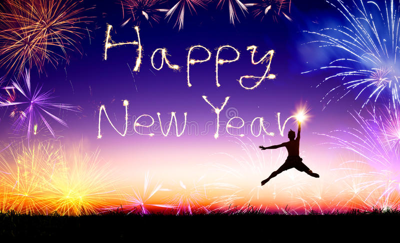 Man jumping and drawing the happy new year. Young man jumping and drawing the happy new year stock photography