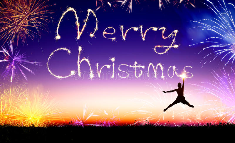 Man jumping and drawing the merry christmas. Young man jumping and drawing the merry christmas royalty free stock images