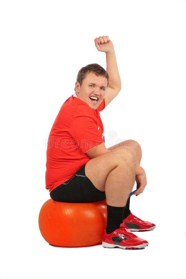 Man jumping on fitness sphere stock photo