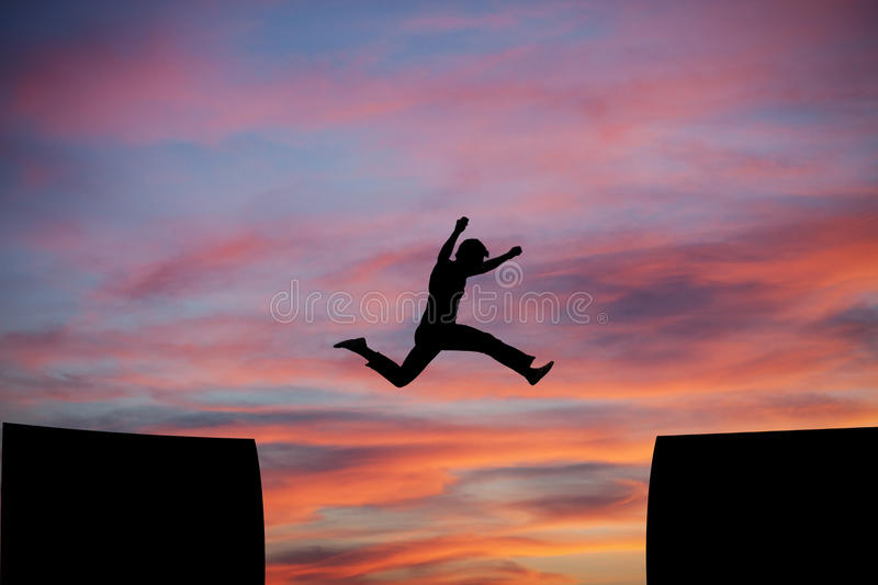 Man jumping a gap in sunset sky. Silhouetted man jumping a gap in sunset sky royalty free stock photos