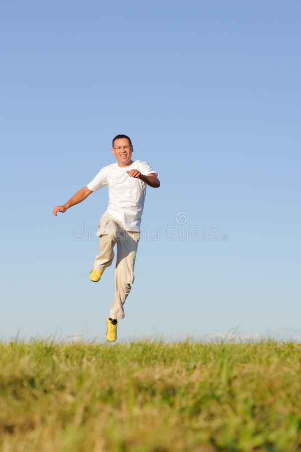 Man jumping on green field stock images