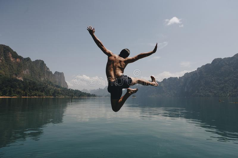 Man jumping with joy by a lake royalty free stock photos