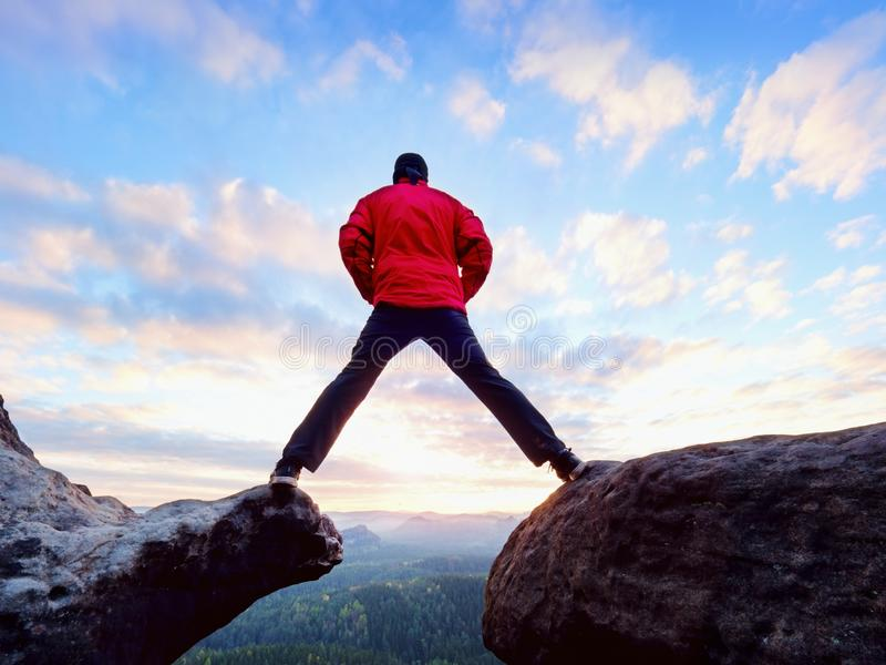 Man jumping from the mountain edge. Man jumping off a cliff without rope. Risky moment. Rough rocky ground stock photography