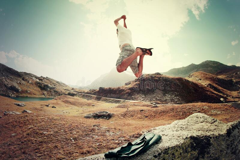 Man jumping in mountains stock images