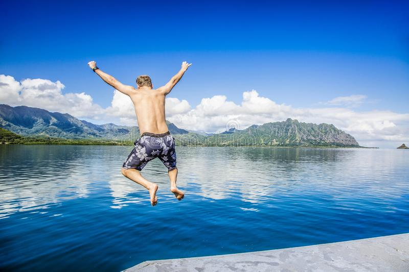 Man jumping into the ocean while on a beautiful scenic Hawaiian vacation. Thrilling and exciting experience. Concept about holiday, success, accomplishment and royalty free stock image