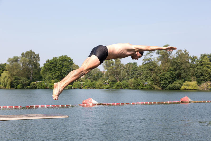 Man Jumping Off Diving Board At Swimming Pool Stock Photo