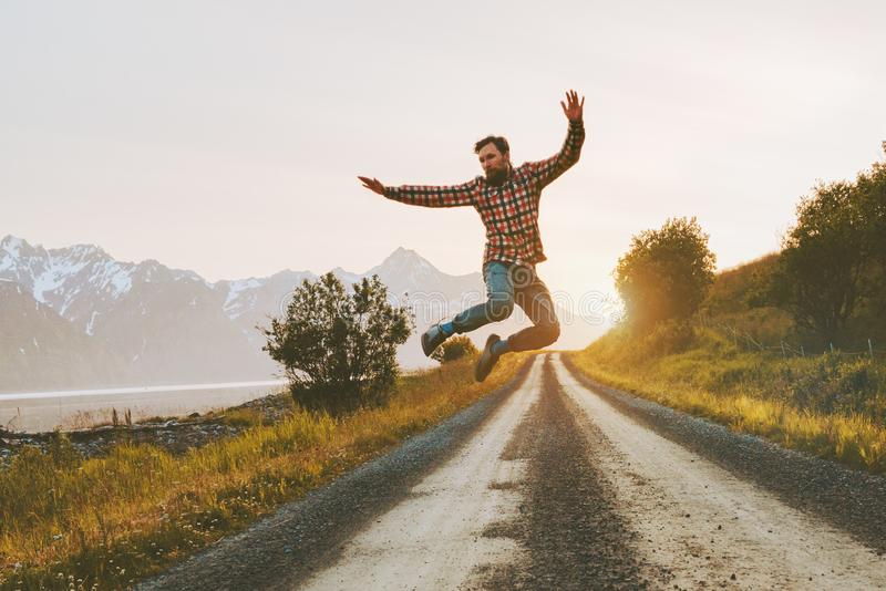 Man jumping over mountain road outdoor travel lifestyle. Adventure vacations activity in Norway freedom success concept happy positive vibes emotions stock images