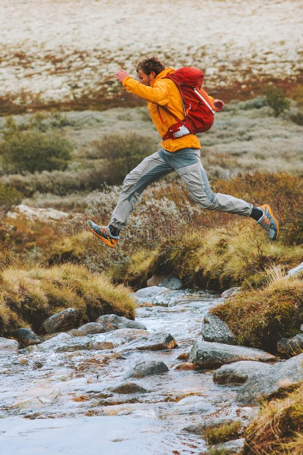 Man jumping over river in mountains hike travel adventure active stock photos