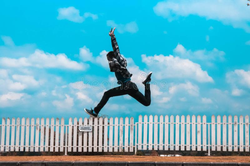 Man Jumping over White Fence royalty free stock photography