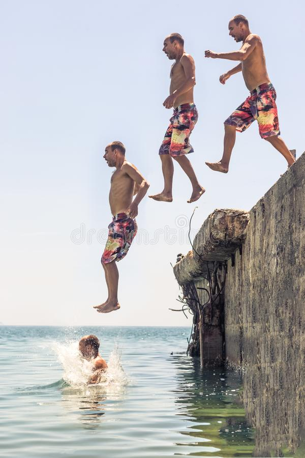 Man jumping from pier stock photos